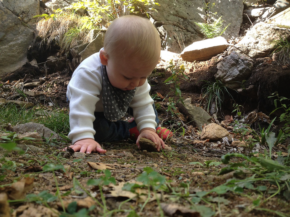 Baby playing with rock, Photo by Monica, on Instagram @mamanonthetrail