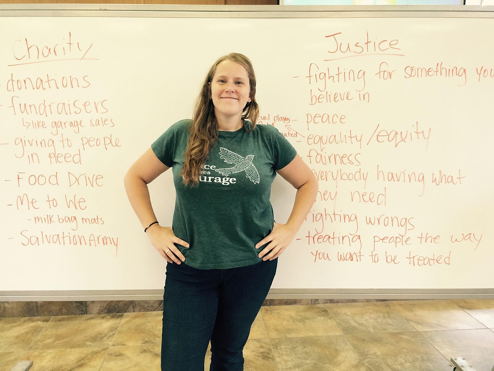Elle Crevits standing in front of white board after speaking to youth at Peace Camp. White board outlines the difference between Charity and Justice.