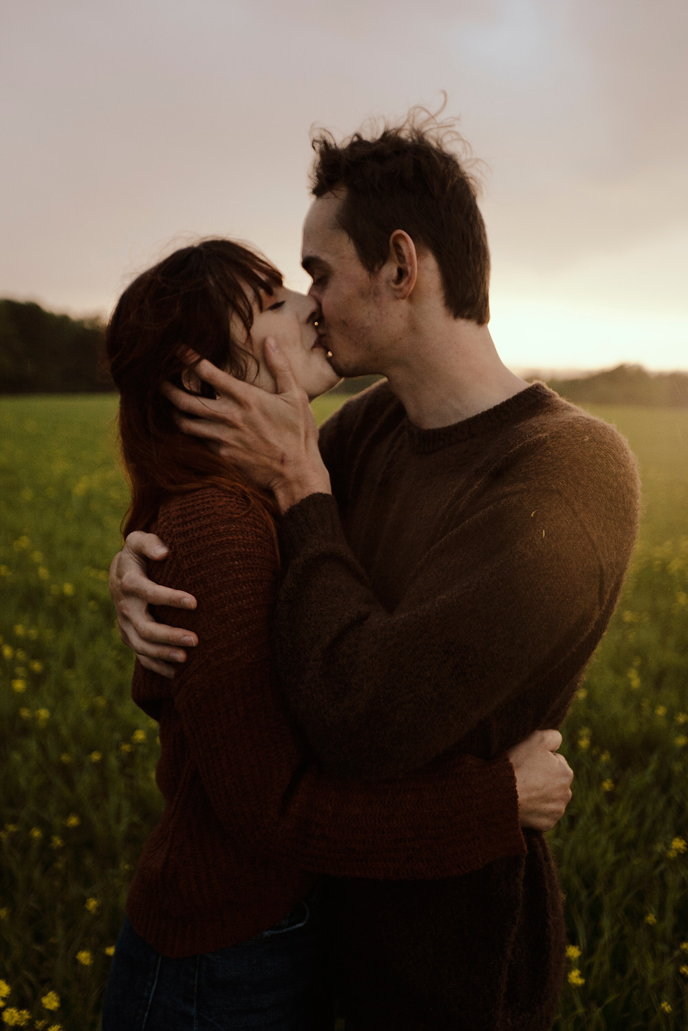 a couple is kissing at sunset on a field in the rain