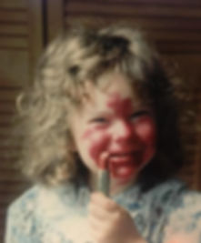 A very old photo of myself when I was little having smeared red lipstick allover my face