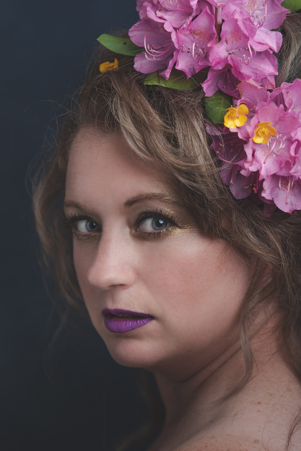A woman in her 40's takes a color self portrait with rhododendrons in her hair.