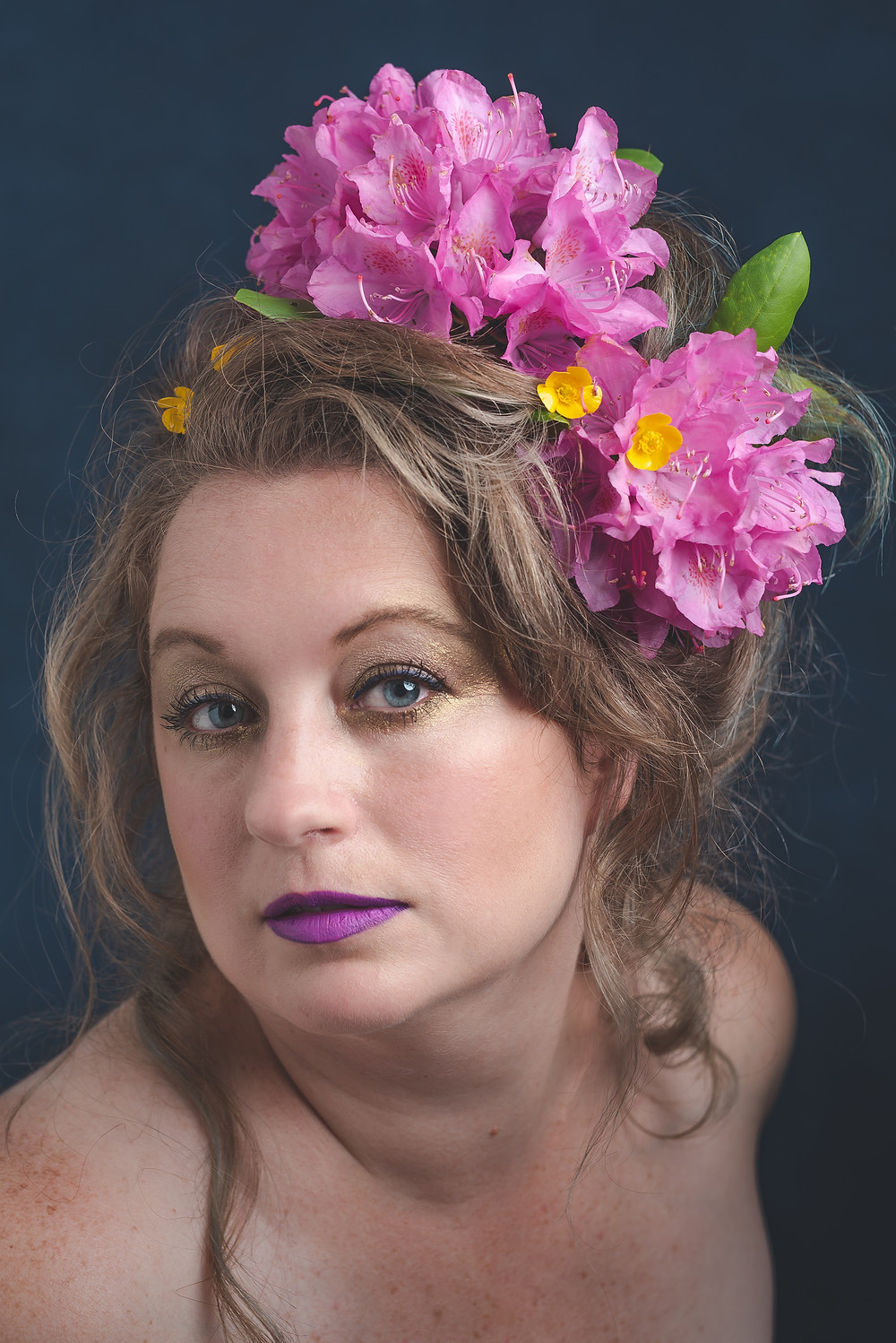 A woman in her 40's takes a color self portrait with rhododendrons in her hair looking straight into camera.