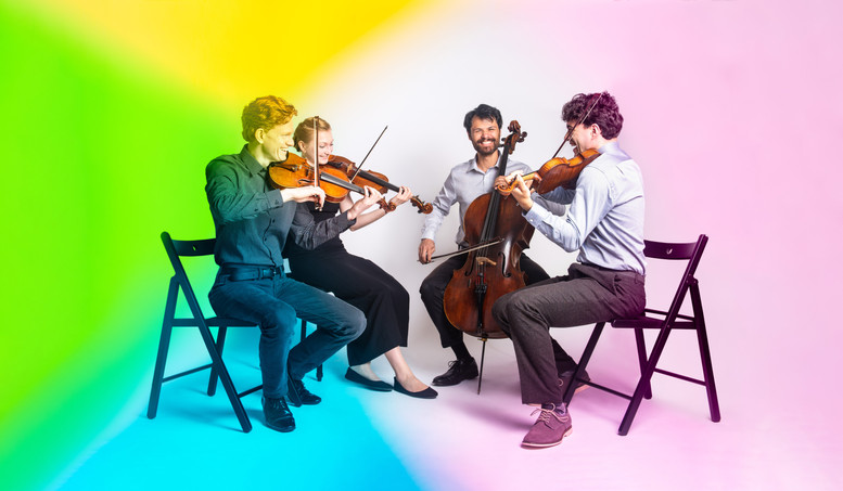 Friction Quartet is seated in front of a white backdrop joyfully playing together. Shades of blue, yellow, magenta, and green appear in the corners of the image from colored gels placed in front of the camera lens.   Photo by Bonnie Rae Mills.