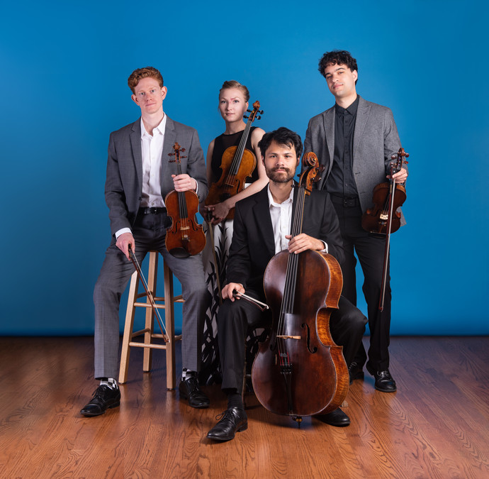 Friction Quartet poses with their instruments in a tiered arrangement, with some members seated at various heights, with others standing.  Photo by Bonnie Rae Mills.