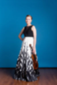Press photo of violist Lucia Kobza of Friction Quartet. She holds her instrument at her side and wears a gown featuring inky vines that arise from the hem of her skirt.