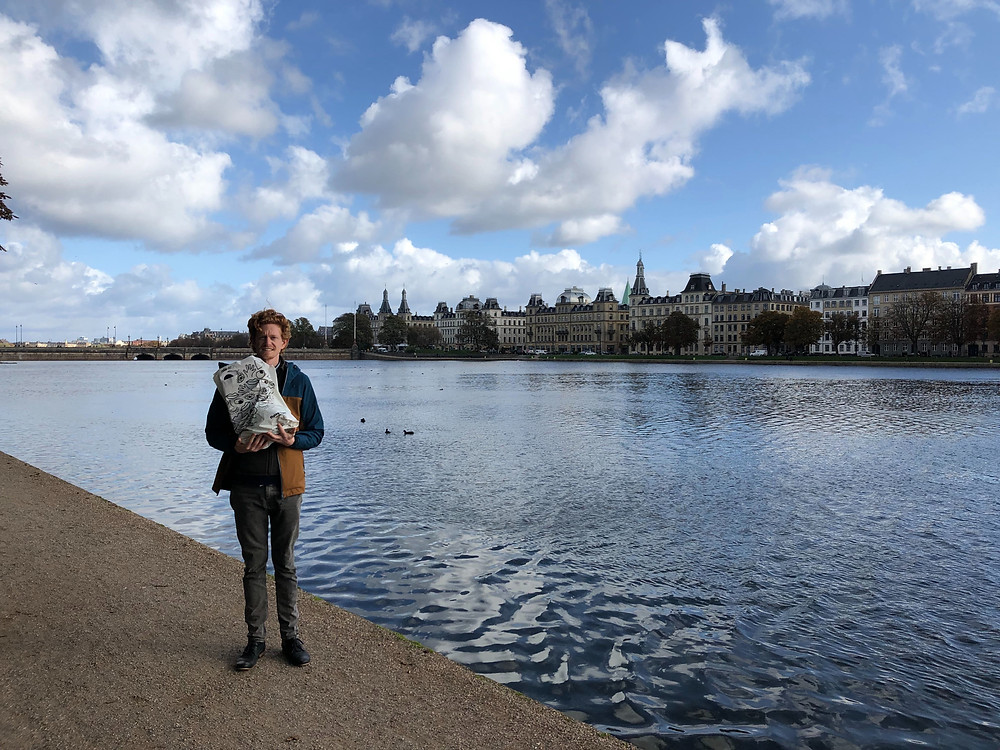 Kevin of Friction Quartet holding a bag of groceries next to the river in Denmark.