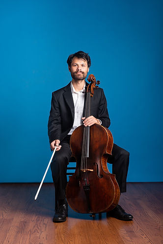 Press photo of Doug Machiz of Friction Quartet wearing a black suit and holding his cello.