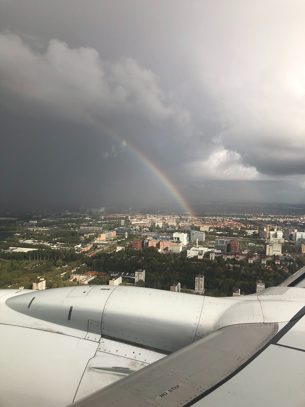 Plane landing in Denmark with a rainbow visible over the city.