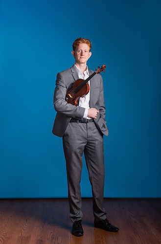 Press photo of violinist Kevin Rogers of Friction Quartet wearing a grey suit with his violing tucked in the crook of his arm.