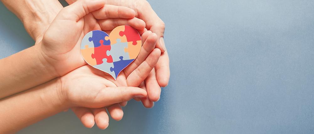 Aikuinen pitää käsissään lapsen käsiä, lapsen käsissä on palapelin paloista koottu sydän.