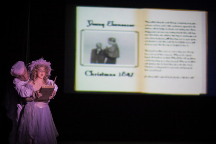 Ghost of Christmas Past showing Ebenezer Scrooge what's in his life book.  Glimpses of the past.