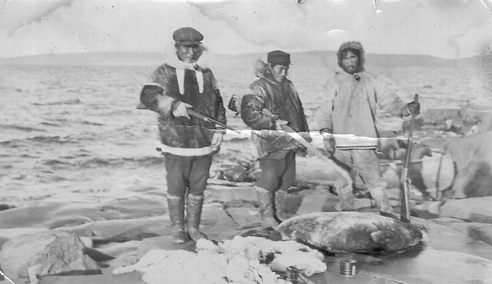 Inuit holding rifles over dead seals Ang
