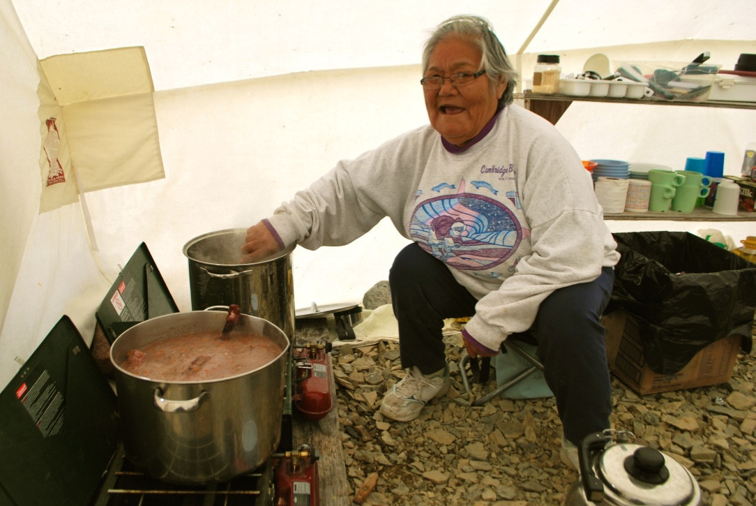 Anna Nahogaloak prepares a pot of caribou stew for hungry land camp participants. Photo by Brendan Griebel.