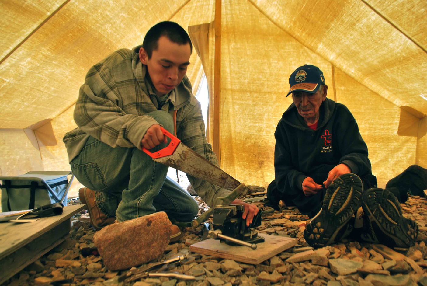 Jimmy Maniyogina teaches Ben Kaniak to prepare caribou antler for the handle of an ulu knife. Photo by Brendan Griebel.