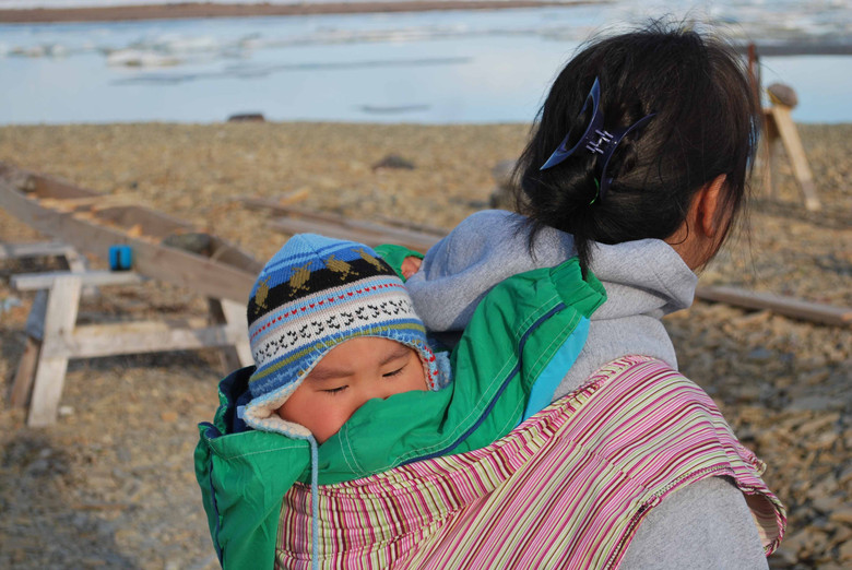 A baby visits a traditional land camp tucked into a packing shirt. Photo by Brendan Griebel.