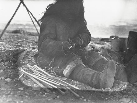 Inuk man making arrows at Armstrong Poin