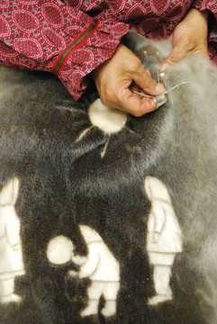 A wallhanging for display in the Inuinnauyugut exhibit is sewn from various colours of seal skin. Photo by Brendan Griebel.