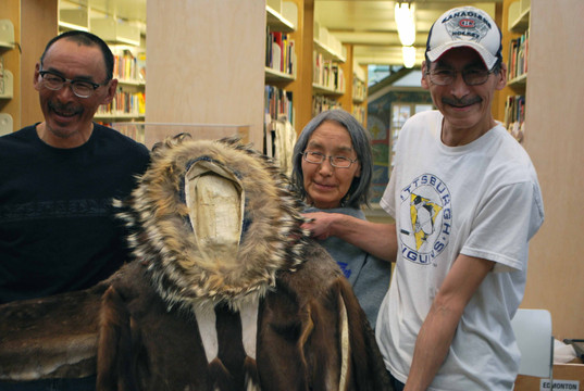 The family of May Hakongak hold up one of her parkas donated to the KHS by the Prince of Wales Heritage Centre. Photo by Brendan Griebel.