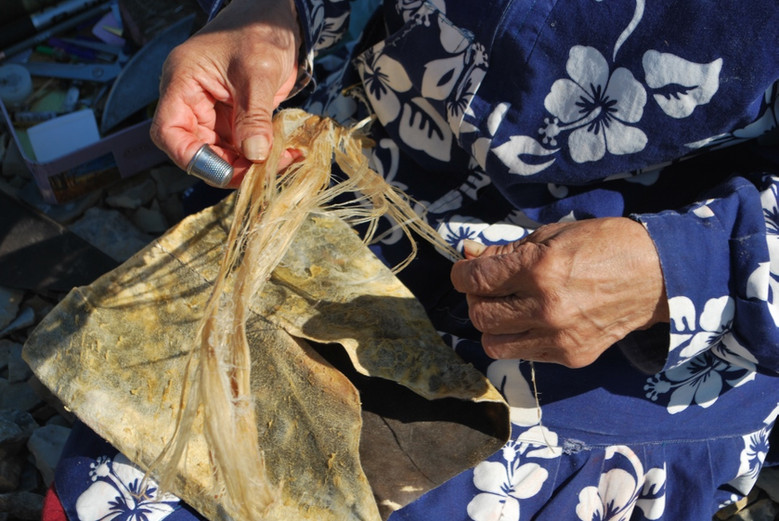 Mary Kaniak uses caribou sinew as thread for her sewing. Photo by Brendan Griebel.