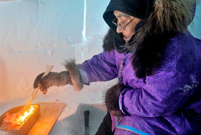 annie atigihioyak tends the qulliq lamp.