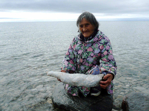 Mary Kaniak prepares a traditional bag using heather and the skin of an Arctic char. Photo by Brendan Griebel.