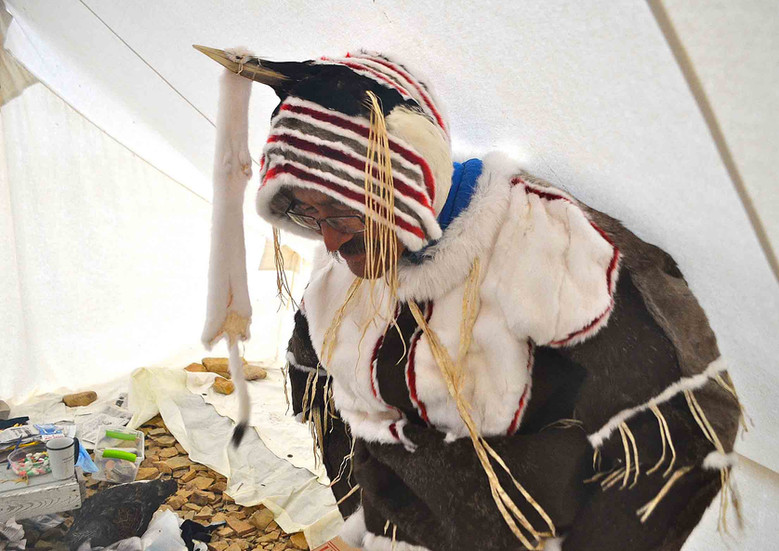 Simon Qingnaqtuq prepares to perform in a traditional Inuinnait dance suit. Photo by Brendan Griebel.