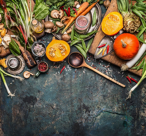 Pumpkin with vegetarian cooking ingredients, wooden spoon on dark rustic background, top view, borde