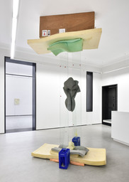 Chaudfontaine,  2017, glass, cement, polyurethane foam, wood, plastic crates, pencil, rubber spacers, 15 x 9 x 7 feet (height variable)  Sculpture uses tension to stand, as a shipping crate appears to be pressed against gallery ceiling by two tall panels of glass. An anthropomorphic form (foam saturated with cement) is suspended between the glass pieces that push into it. Lighghts 2014 in background, at Galerie Christophe Gaillard in Paris. Photo by Rebecca Fanuele