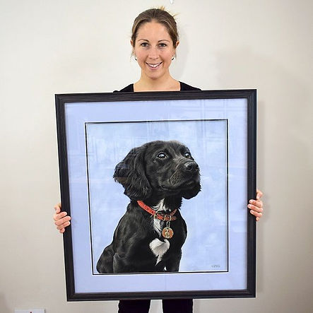 Dog portrait artist Naomi Jenkin holding the framed portrait of Mabel the working Cocker Spaniel puppy.