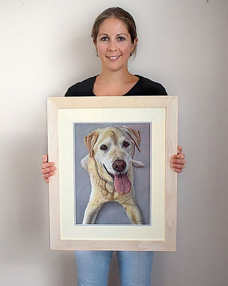 Dog portrait artist Naomi Jenkin with the framed portrait of Dylan the Golden Labrador.