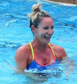 בחורה מחייכת בשיעור התעמלות במים בבריכה