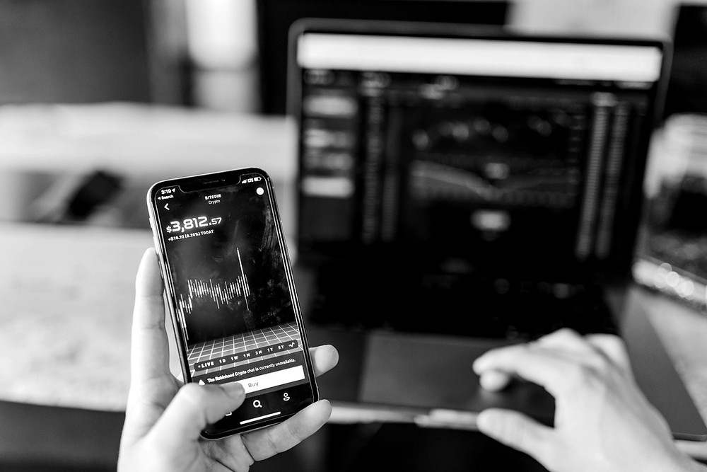 Mobile phone with image of energy market data and laptop with image of energy market data. Photo by Austin Distel on Unsplash.