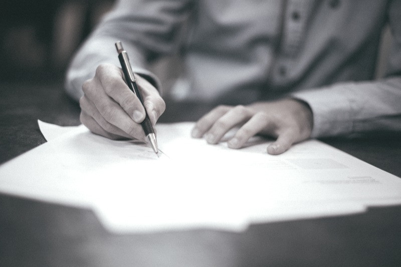 Hand holding a pen signing a gas and electricity contract