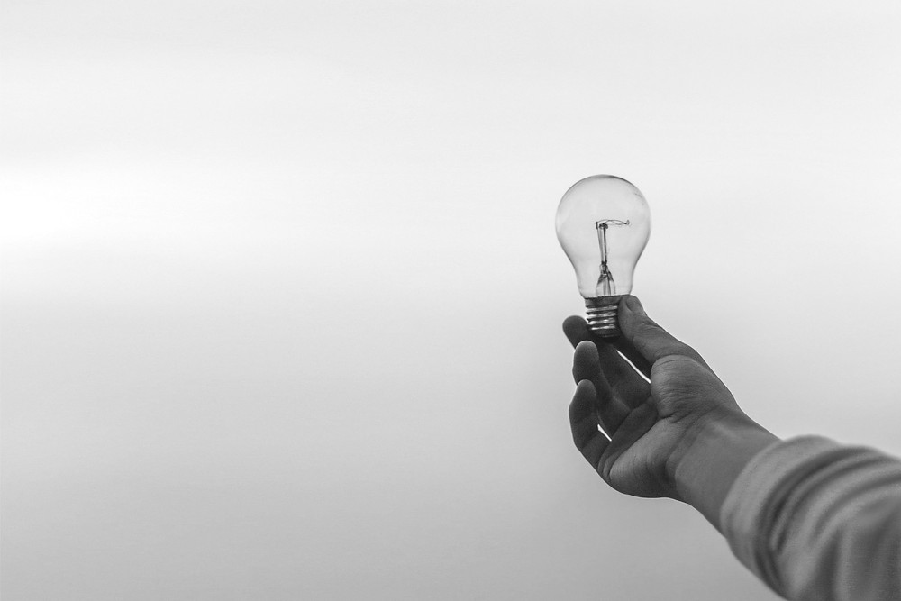 Person's hand holding a lightbulb.