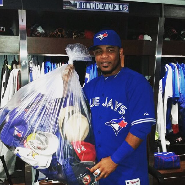 Edwin Encarnacion holding hats Jays fan threw onto the field after hitting his third home run of the afternoon