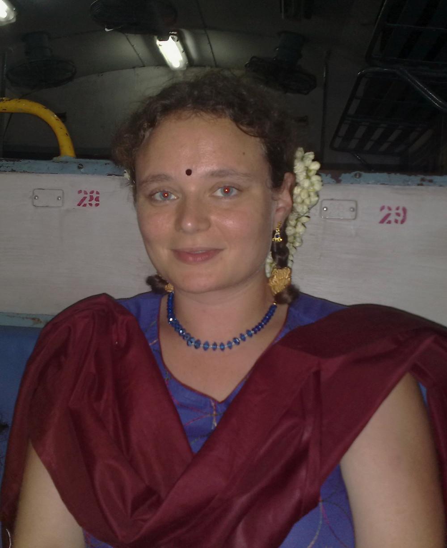 Eva sitzt mit Jasmin-Blüten im Haar, Bindi und traditioneller indischer Kleidung im Zug.