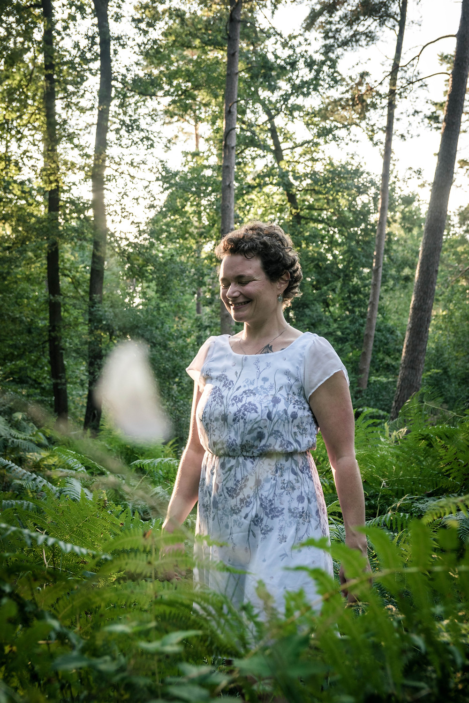 Eva geht in hellem Sommerkleid durch hohes Farn