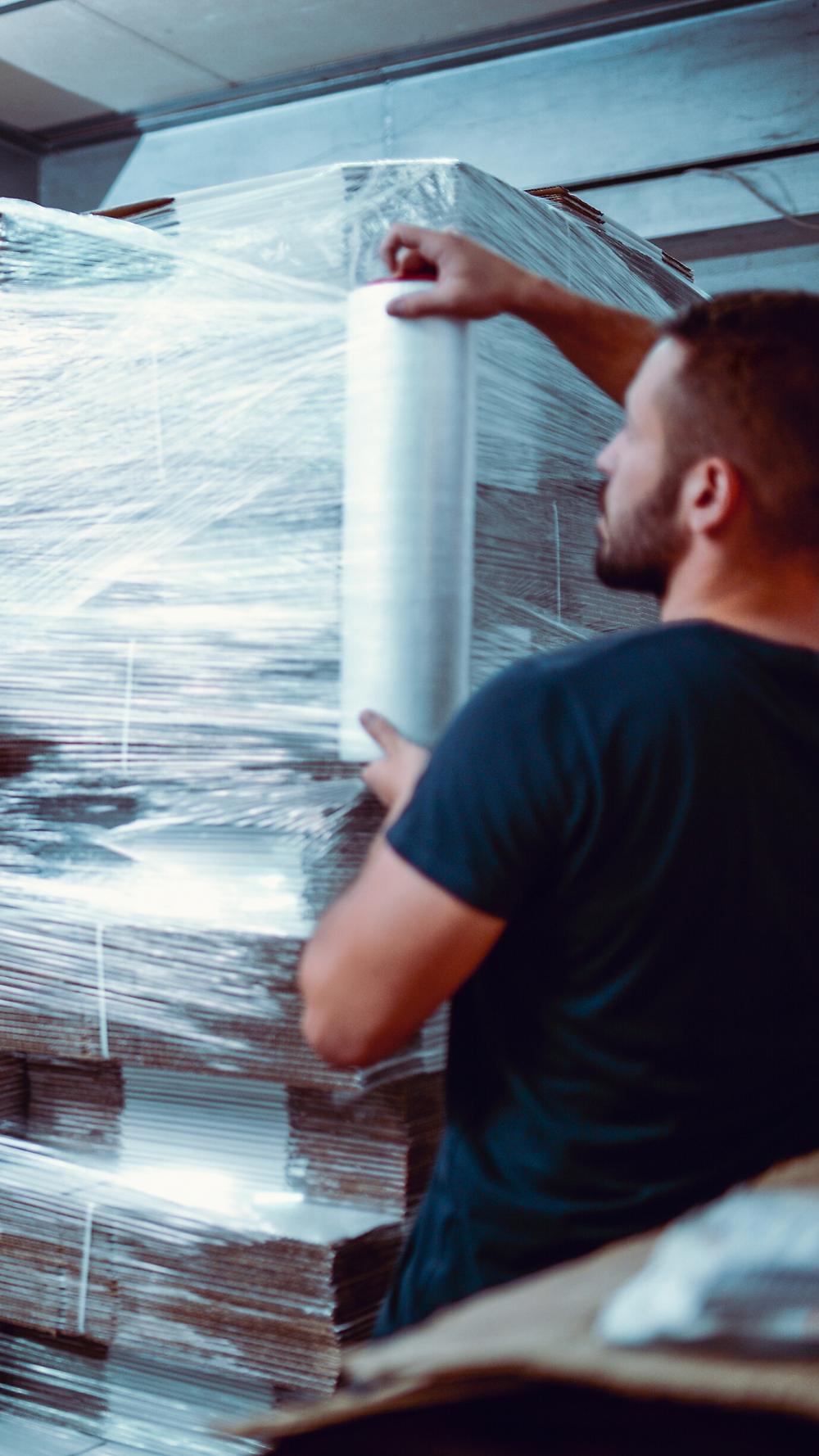 Mann umspannt eine beladene Palette mit durchsichtiger Folie, Quelle: Canva