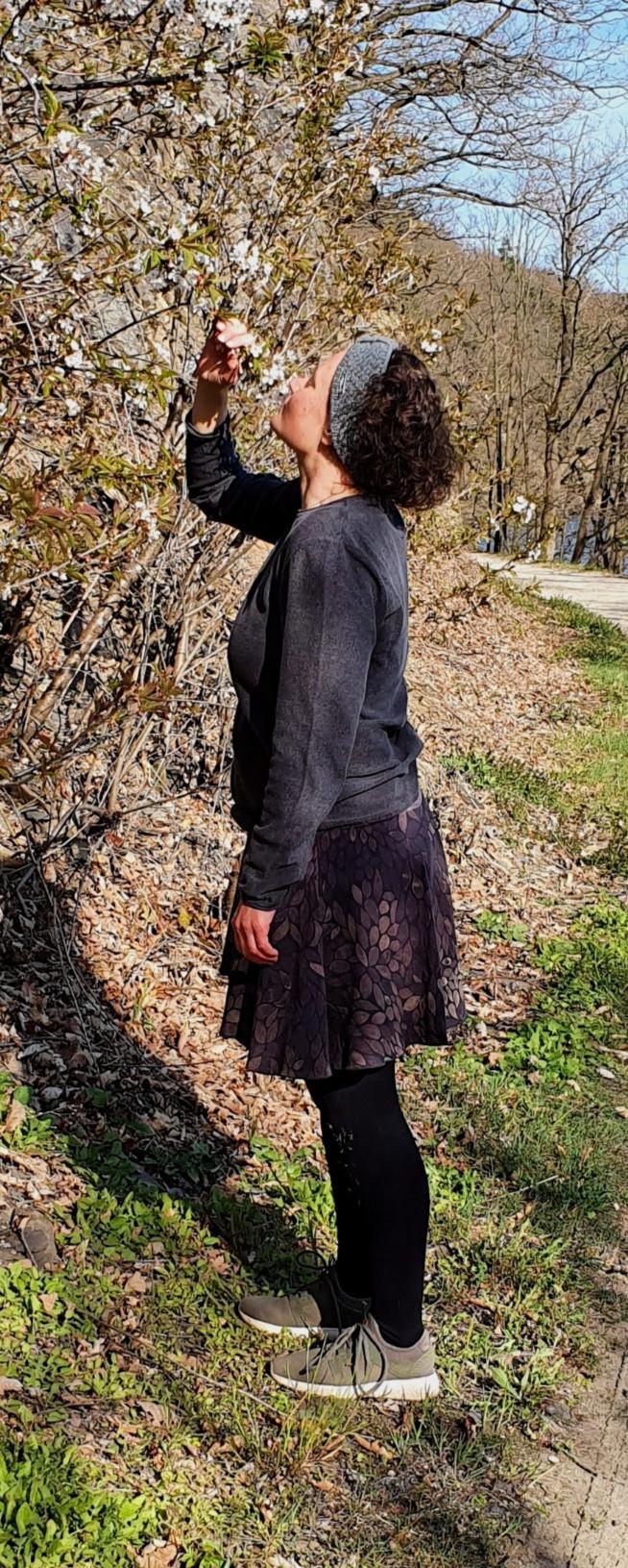 Eva steht vor einem Kirschbaum und riecht an einer Blüte Foto: Tabea