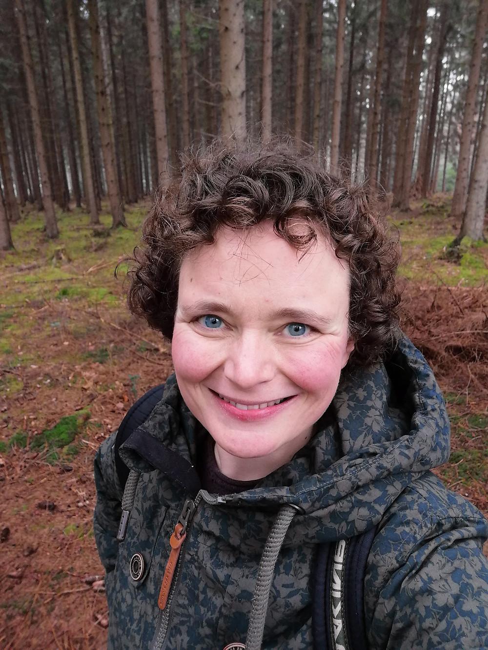 Eva steht strahlend im Wald