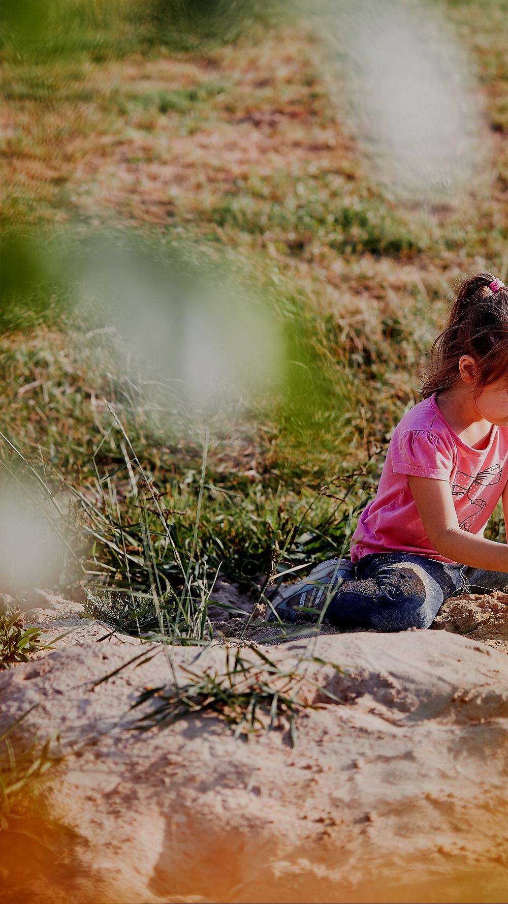 Mädchen sitzt in der Natur (Sand und Wiese), Quelle: Canva