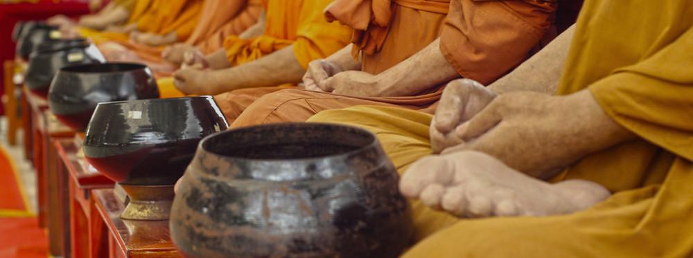 Mönche sitzen meditierend vor Spenden-Schalen; Foto: Getty Images