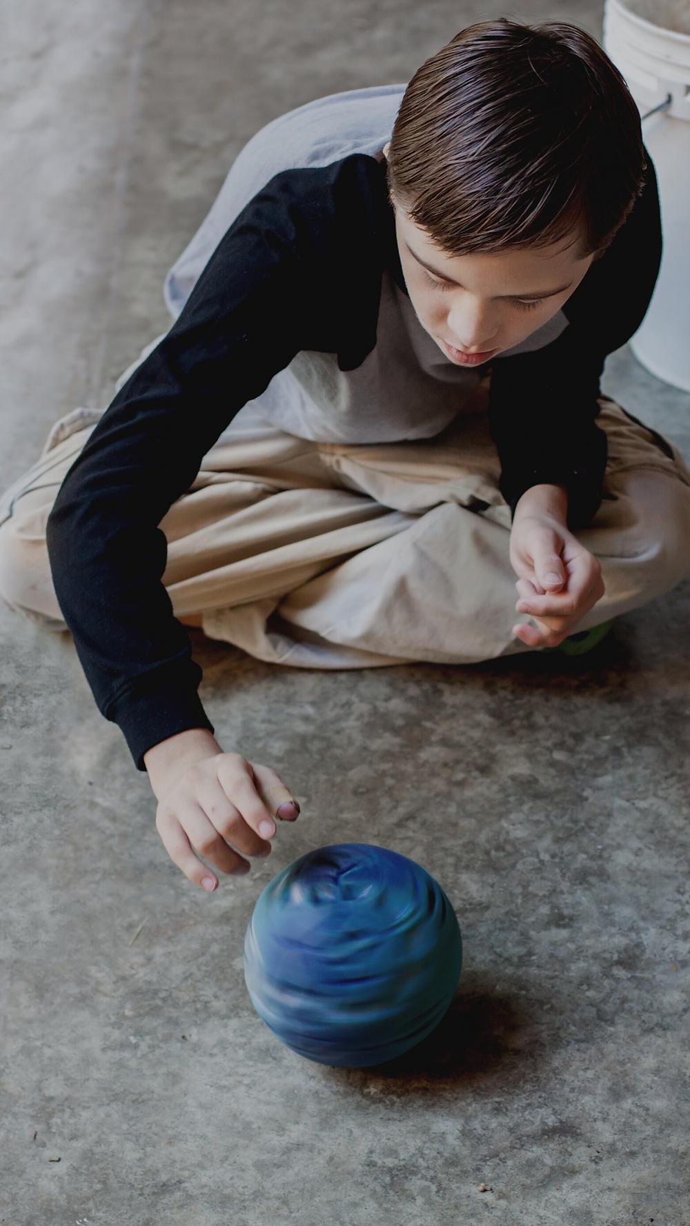 autistisches Kind sitzt im Schneidersitz auf dem Boden und dreht eine blaue Kugel, Quelle: Canva