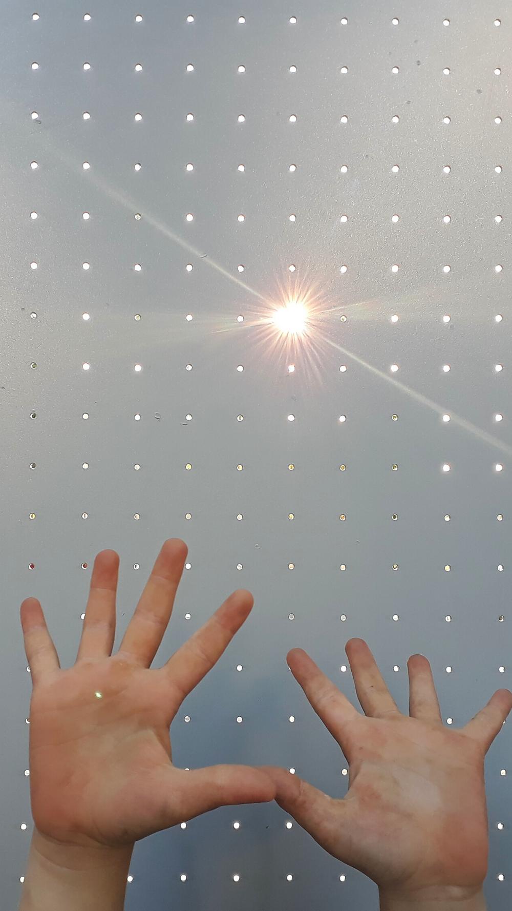 Zwei kleine Hände, die im Licht der Sonne, welches durch eine gepunktete Scheibe einfällt, spielen