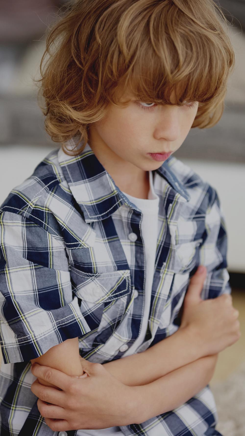 Kind mit vor der Brust verschränkten Armen und herabgesenktem, mürrisch wirkendem Blick, Quelle: Canva