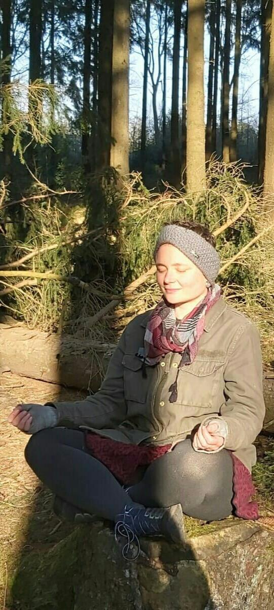 Eva sitzt meditierend im Wald; Foto: Hema Alexandra Junblut