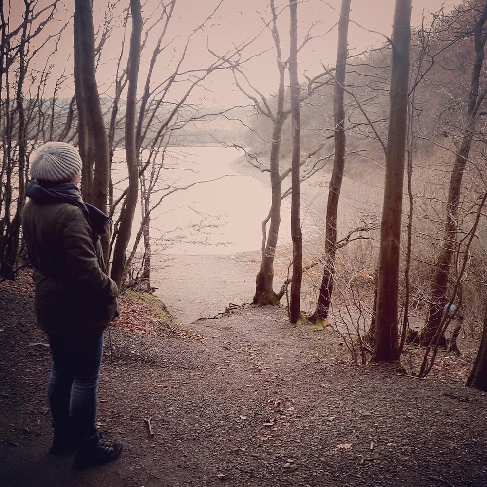 Eva im Herbst bei diesigem Wetter am Ufer eines Sees. Sie blickt weg von der Kamera in die Ferne. Foto: Sandra