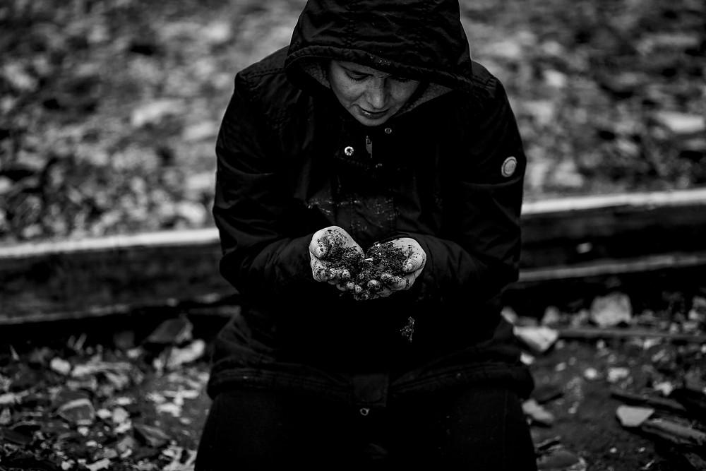Eva hockt im schwarzen Mantel auf dem Boden, blickt auf ihre Hände, in denen sie Erde hält; Foto: Rosa Engel