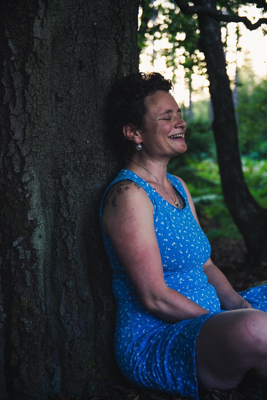 Eva sitzt im sommerlichen Kleid mit dem Rücken an einen Baum gelehnt. Mit geschlossenen Augen lacht sie vergnügt. Foto: Judygrafie