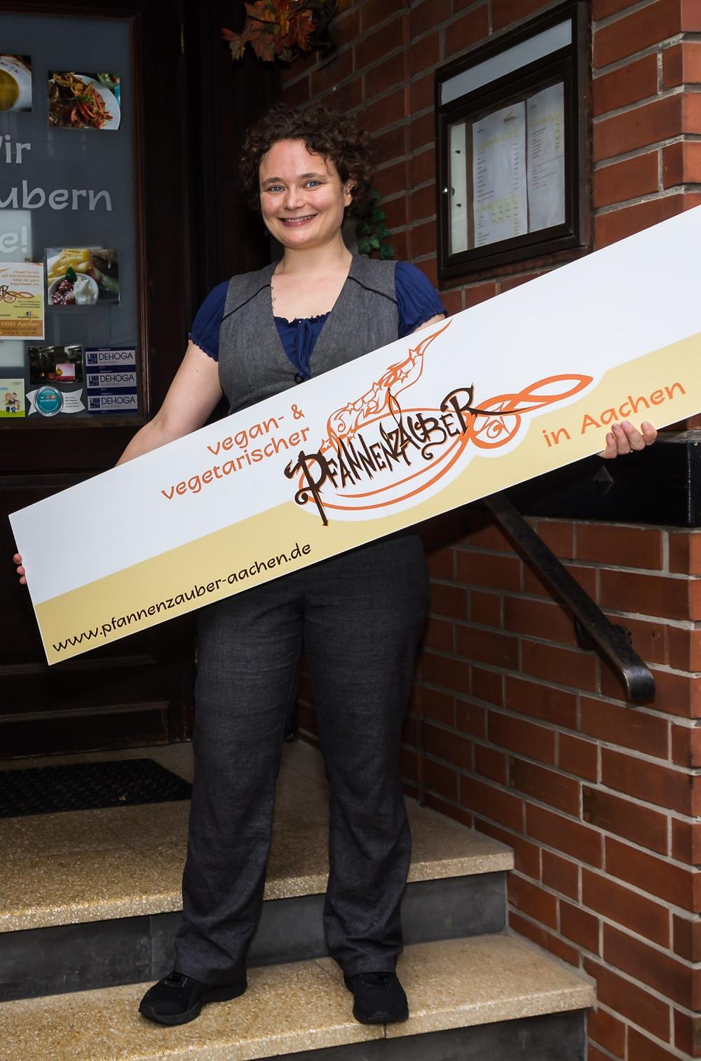Eva steht mit einem großen Schild vor der Eingangstür ihres Restaurants Pfannenzauber. Auf dem Schild ist das verschnörkelte Logo zu sehen